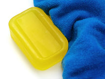 Soap Series 7. Yellow bar of semi-transparent soap next to a fluffy blue towel Royalty Free Stock Image