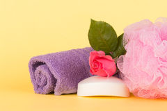 Soap topped with pink rose next to a shower puff and wash cloth Stock Images