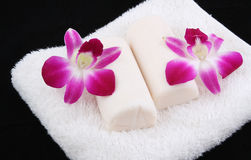 Soap on towel. Closeup two white soap and two orchid on white towel Stock Photo
