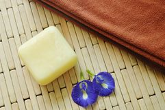 Soap and towel with blue pea violet flower on bamboo mat Royalty Free Stock Images