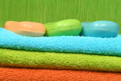 Soap and towels. Bath and spa accessories - three colorful towels and soap Royalty Free Stock Image