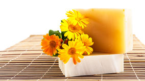 Soap and yellow marigolds on bamboo table mat Royalty Free Stock Image