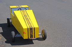 Soapbox Derby Cart Racer. A yellow soapbox derby race cart on a racing track Stock Photo