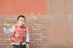 Soapbubbles мальчика дуя Стоковая Фотография