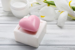 Soaps and cosmetic cream with beautiful flowers on wooden table, Royalty Free Stock Photography