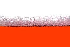Soapy Bubbles. Orange soap bubbles white background Royalty Free Stock Image