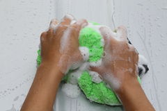 Soapy hands with green sponge Royalty Free Stock Photos