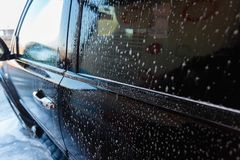 Soapy water drains from the car. A man washes a hand car wash with water under pressure in a car wash outside in a hangar for a ca. R wash Royalty Free Stock Photo