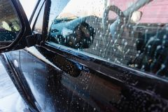 Soapy water drains from the car. A man washes a hand car wash with water under pressure in a car wash outside in a hangar for a ca. R wash Stock Photo