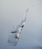 Soaring glass with water and splash. Glass of clear water flies through the air and splashes Stock Photos