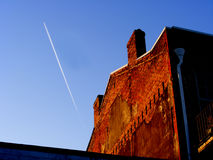 Soaring High. Creative image of aircraft in high flight and an older building Stock Images