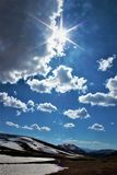 Soaring Sunburst. The sun bursts across the mountain sky, speckled with migrating cumulus clouds nearby Aspen, Colorado. Snow striates the sloping mountainside Royalty Free Stock Images