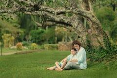 Sob a árvore na grama sente a mãe e o filho Fotografia de Stock