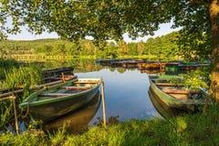 Sob as árvores, barcos no porto no lago Imagem de Stock
