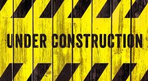 Sob as listras pretas amarelas do texto do sinal de aviso da construção pintadas no fundo largo do panorama da textura de madeira fotografia de stock