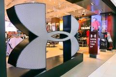 SOB a empresa americana do sportswear da ARMADURA fundada em 1996 fabrica esportes dos calçados e a roupa ocasional abre a loja g fotografia de stock