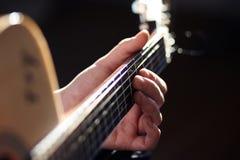 Sob a iluminação brilhante, uma pessoa joga uma melodia da guitarra fotos de stock royalty free