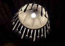 Sob a lâmpada iluminada decore com forquilha e faca da colher Fotos de Stock