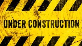 Sob o texto do sinal de aviso da construção com as listras pretas amarelas pintadas no fundo largo do panorama da bandeira da tex imagem de stock royalty free
