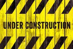 Sob o texto do sinal de aviso da construção com as listras pretas amarelas pintadas no fundo largo da textura de madeira da pranc fotografia de stock