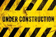Sob o texto do sinal de aviso da construção com as listras pretas amarelas pintadas no fundo largo da textura de madeira da pranc imagens de stock royalty free