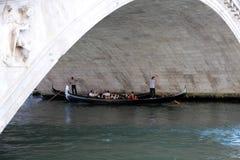 Sob a ponte de Rialto com dois gondoleiros e suas gôndola Fotografia de Stock Royalty Free