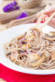 Soba with mushrooms and onion on chopstick Stock Image