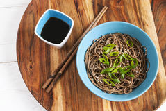 Soba noodles in a bowl with chopsticks and soy sause. Top view Stock Images