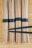Soba noodles and chopsticks on bamboo background Royalty Free Stock Photography