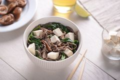 Soba noodles with spinach and tofu. Main course combined with shiitake mushrooms and cup of green tea. Meatless meal, Asian cuisine stock image