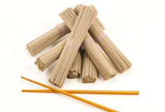 Soba noodles whit chopsticks on white background. Soba noodles and chopsticks on white background, horizontal, cenital picture Stock Images