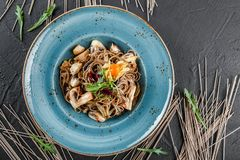 Soba noodles with wild mushrooms in sweet and sour sauce, onions and greens in plate on dark stone background. Vegetarian food.  royalty free stock image