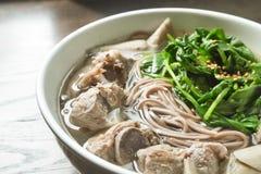 Soba nudel i buljong för grisköttstöd med spenat Arkivbild