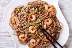 Soba with shrimp and chopsticks  close-up. horizontal top view Stock Photos