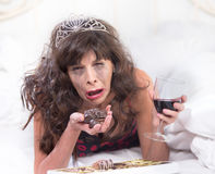 Sobbing Woman in Tiara Drinking Wine and Cramming Chocolates in Royalty Free Stock Photo