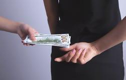 Soborno del dinero de manos de detrás fotografía de archivo