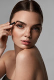 Sobrancelhas de contorno da mulher 'sexy' bonita Composição glamoroso imagem de stock