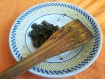Sobras de Palak Saag en una placa de cerámica con la cuchara de madera foto de archivo