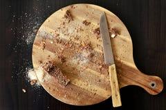 Sobras del desayuno, migajas de pan en la tabla de cortar fotografía de archivo