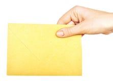 Sobre amarillo en la mano Foto de archivo libre de regalías