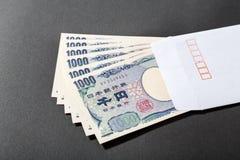 Sobre blanco y billete de banco japonés 1000 yenes Fotografía de archivo