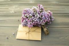 Sobre con las ramas de la lila Fotos de archivo
