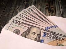 Sobre con los dólares de EE. UU. en la tabla de madera imagen de archivo