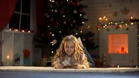 Sobre de la tenencia de la niña con la letra para Papá Noel, creencia en magia de Navidad imagenes de archivo