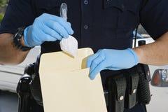 Sobre de las pruebas de Putting Cocaine In del oficial de policía Foto de archivo libre de regalías