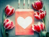 Sobre de papel con el corazón, las flores preciosas frescas y los marcadores del cepillo, visión superior, espacio de los tulipan Imagen de archivo libre de regalías