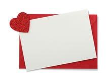Sobre de papel rojo con la tarjeta y el corazón blancos Imágenes de archivo libres de regalías