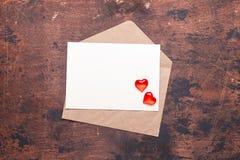 Sobre del arte con los corazones rojos en una endecha plana del fondo del vintage del trozo de papel del concepto de madera del d fotos de archivo libres de regalías