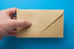 Sobre del control de la mano del hombre en fondo azul imagen de archivo libre de regalías