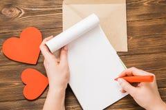 Sobre del papel de Kraft con el corazón rojo de madera en la tabla de madera con Fotografía de archivo libre de regalías